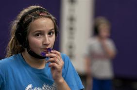 Erica Chapman, 11, readjusts her mouth piece after wrestling her partner Thursday at Bloomington South High School. Photo by Mark Felix.